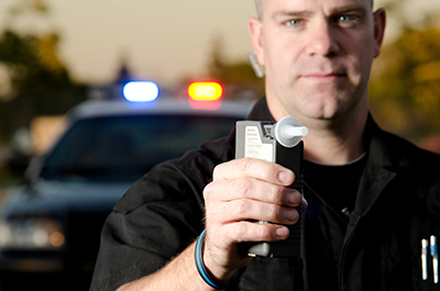 police officer holding device for breathalyzer test